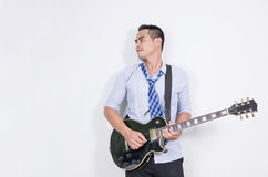Relaxing asian business man playing electric guitar near the white wall stock image