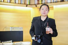 Relaxing Asian photographer holding beverage and camera royalty free stock photography