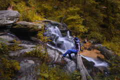 Relaxing by an autumn waterfall Stock Photo