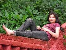 Relaxing Babe. A young indian babe relaxing on a bricked wall Royalty Free Stock Images