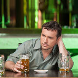 Relaxing at the bar. Portrait of depressed young men drinking be Royalty Free Stock Images