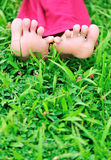 Relaxing barefeet. Womans barefeet relaxing on green grass Royalty Free Stock Photo