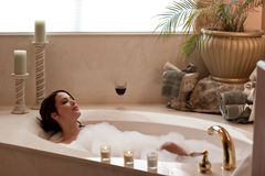 Relaxing in the bath. Young pretty lady relaxing in a bubble bath Royalty Free Stock Image
