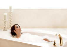 Relaxing in the bath. Young attractive woman relaxing in a bubble bath Stock Photos