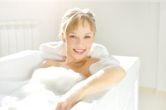 Relaxing in bath. An Attractive girl relaxing in bath on light background Stock Photos