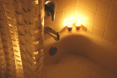 Relaxing Bath. A Bubble bath lit by candle light Royalty Free Stock Images