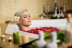 Relaxing in bath with petals. Beautiful woman relaxing in bath with petals stock photos