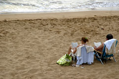 Relaxing at beach. Couple relaxing on a sunny day at a beach Royalty Free Stock Photography