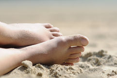 Relaxing at the beach. Shot of feet in the sand of woman relaxing at the beach Stock Photo