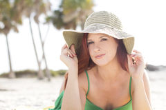 Relaxing at the beach. A beautiful woman wearing a sun hat relaxing at the beach Royalty Free Stock Photos