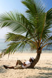 Relaxing at the beach. A man relaxing at the beach under a palm tree stock photos