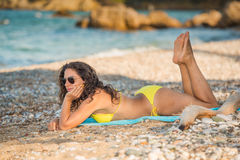 Relaxing on the beach. Attractive young brunette relaxing on the beach wearing sunglasses and yellow bikini holding her legs and feet up stock photography