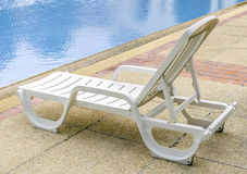 Relaxing beach chair beside of blue swimming pool Royalty Free Stock Images