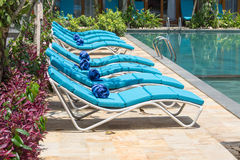Relaxing beach chairs and swimming pool Stock Images