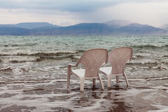 Relaxing on the beach. Relaxing on deserted, remote, not crowded beach. Two white beach chairs stand in the sea, nobody Royalty Free Stock Images