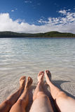 Relaxing beach feet. Young couple relaxing at the side of the tranquil lake royalty free stock image