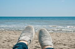 Relaxing on the beach. Feet wearing mint color shoes on the sand beach somewhere in Spain royalty free stock photography