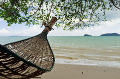 Relaxing beach holiday. A hanging hammock by the beach in an island holiday Stock Photo