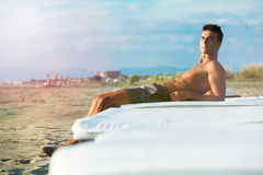 Relaxing on the beach, holiday lounge. Relaxed seaside. Beach holiday. A young man is relaxed on a white mattress on the beach. Atmosphere afternoon before royalty free stock images