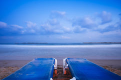 Relaxing at the beach (Horizontal). Relaxing at the beach, two beach chairs, calm blue sea and gentle clouds Royalty Free Stock Images