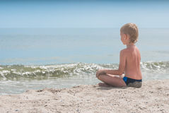 Relaxing on a beach 1. Little boy relaxing in lotus yoga pose on a beach sand with waves and seascape as background Stock Images