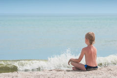 Relaxing on a beach 2. Little boy relaxing in lotus yoga pose on a beach sand with waves and seascape as background Royalty Free Stock Photos