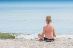 Relaxing on a beach. Little boy relaxing in lotus yoga pose on a beach sand with waves and seascape as background Stock Photography