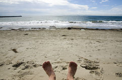 Relaxing on the beach. Relaxing with sandy feet lies on the beach Royalty Free Stock Photography