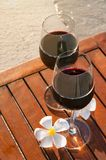 Relaxing beach scene: two glasses of red wine at sunset near water stock photos