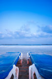 Relaxing at the beach (Vertical). Relaxing at the beach, two beach chairs, calm blue sea and gentle clouds Royalty Free Stock Photo