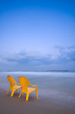 Relaxing at the beach (Vertical). Relaxing at the beach, two yellow chairs, calm blue sea and gentle clouds Royalty Free Stock Photos