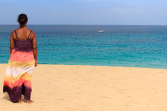 Relaxing beach woman look at a boat Royalty Free Stock Images