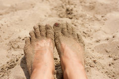 Relaxing at a beach, young woman feet in the warm sand. Relaxing at a beach, young woman feet in the warm yellow sand royalty free stock image