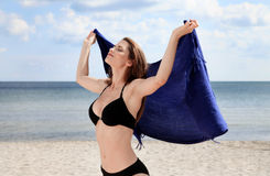 Relaxing on the beach. Young woman on the beach holding a scarf in her hands raised up Stock Photos