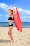 Relaxing on the beach. Young woman on the beach holding a scarf in her hands raised up Royalty Free Stock Image