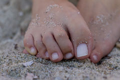 Relaxing at a beach, with your feet in the warm sand. Selective focus royalty free stock photo