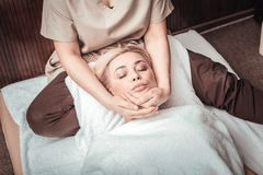 Beautiful blonde woman enjoying her facial massage. So relaxing. Beautiful blonde women closing her eyes while enjoying facial massage stock photography