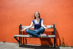 Relaxing beautiful female student breathing in between college exams. Relaxing beautiful female student enjoying sitting on a bench in a yoga lotus position Stock Photography