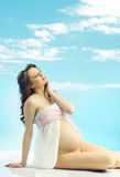 Relaxing beautiful pregnant woman with curly haircut Royalty Free Stock Image