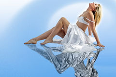 Relaxing beauty. Young woman sitting back relaxing in a conceptual stream of air, sitting on a chrome reflecting pool Stock Photo