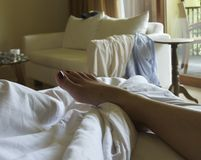 Relaxing in bed. A hotel room where a woman lays relaxed in her bed with just the image of her painted toes and foot revealed Royalty Free Stock Photo