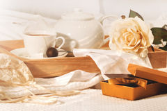 Relaxing in bed with tea and chocolates Stock Photography