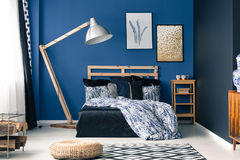 Bedroom in rich blue color. Relaxing bedroom interior in rich blue color with wooden furniture Royalty Free Stock Image