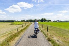 A relaxing bike ride through the beautiful scenery along the river Vecht stock image