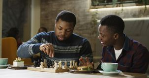 Content black men playing chess in cafeteria. Relaxing black men enjoying free time with refreshing coffee at table and playing chess in leisure Royalty Free Stock Images