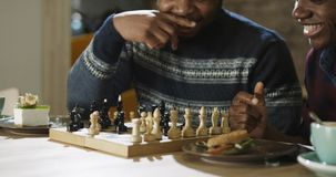 Content black men playing chess in cafeteria. Relaxing black men enjoying free time with refreshing coffee at table and playing chess in leisure Stock Photo