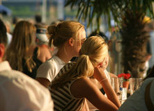 Relaxing blond girls. Two young women relaxing in an outdoor cafe in the warm afternoon sun stock photo