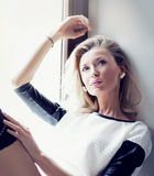 Relaxing blonde young beauty. Romantic young blonde beautiful woman relaxing in home interior on window, looking away Stock Image