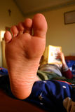 Relaxing with a book. Boy relaxes in his bedroom with a good book. Foot in focus, shallow DOF Royalty Free Stock Photo