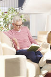 Relaxing with a book. Full length shot of an older man reading book while relaxing at home Stock Photo